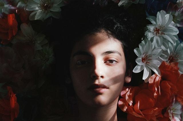 Žena leží medzi farebnými kvetmi a na tvár jej svieti slnko